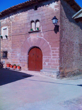 Casa de Arilla. Destaca la fachada de piedra sillar, la ventana geminada y la puerta con frandes dobelas de piedra típica de la zona.