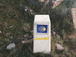 Mojón que indica la dirección de la ruta jacobea.