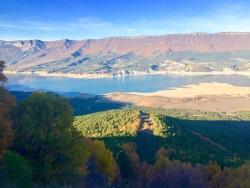 Vista del embalse de Yesa. La sierra de Leyre se aprecia al fondo y en su parte alta se puede ver los colores ocres de un extenso bosque de robles.
